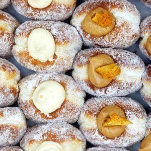 An image of many rows of doughnuts. Vanilla custard doughnuts and honeycomb doughnuts.