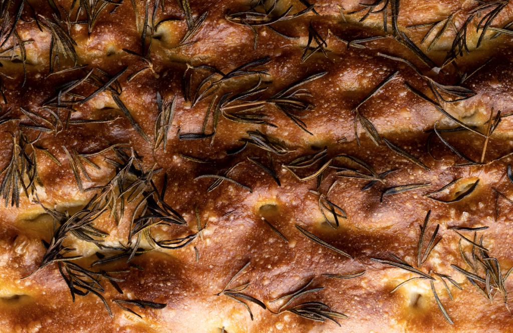 A close up picture of freshly baked italian focaccia bread. The focaccia bread is covered in olive oil and rosemary.