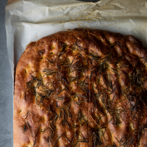 A freshly baked italian Focaccia bread covered in olive oil and rosemary. The focaccia bread is on a baking tray and parchment paper.