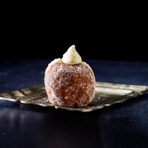Freshly baked Bread Ahead doughnut with a cream filling, positioned on a golden plate. With the dark blue and black background of our London bakery school.