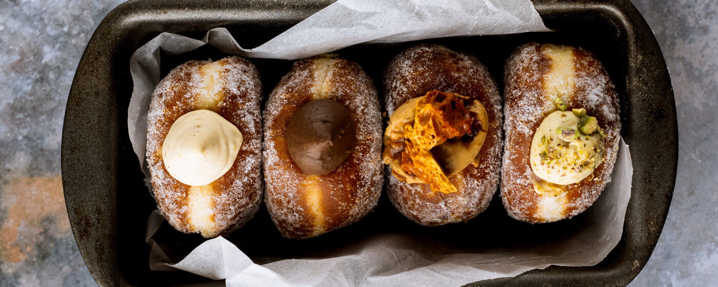 Four Bread Ahead doughnuts that have been freshly made during an online Bread Ahead doughnut baking class. The doughnuts have four different fillings. The first doughnut filling is vanilla custard, the second chocolate, the third salted caramel and the fourth pistachio.
